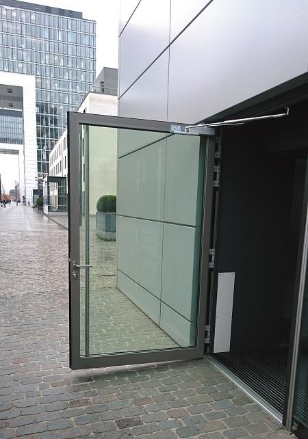 Die große Glas-Eingangstür (ca. 1,45 x 2,4 m, Gewicht ca. 140 kg!) zu einem dieser Verkaufslokale wurde immer wieder durch den Wind unkontrolliert aufgeschlagen. Türöffnungsbegrenzer Glastüre