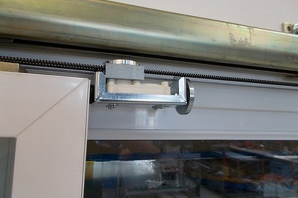 Sliding door closer with freewheel function: in the event of an alarm the carrier casing will close the door