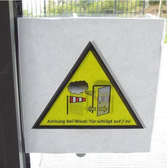 Warnschild Wind schlägt Tür auf